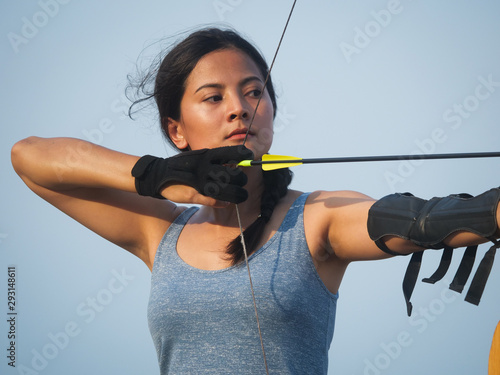 Foto Asian Archery woman with bow shooting on the beach