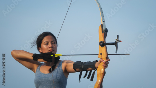 Photo Asian Archery woman with bow shooting on the beach