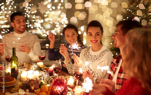 winter holidays and people concept - happy friends with sparklers celebrating christmas at home feast - 293149401