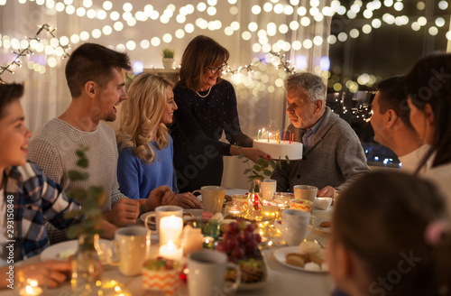 Fototapety, obrazy: celebration and family concept - happy grandfather blowing candles on birthday cake at dinner party at home