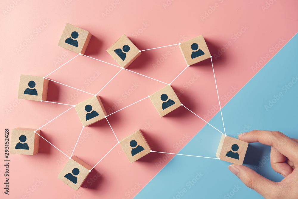 Fototapeta Building a strong team, Wooden blocks with people icon on blue and pink background, Human resources and management concept.