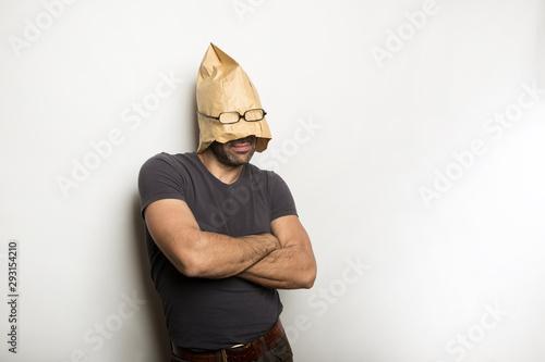 Photo Uomo con busta di carta in testa e braccia conserte su sfondo