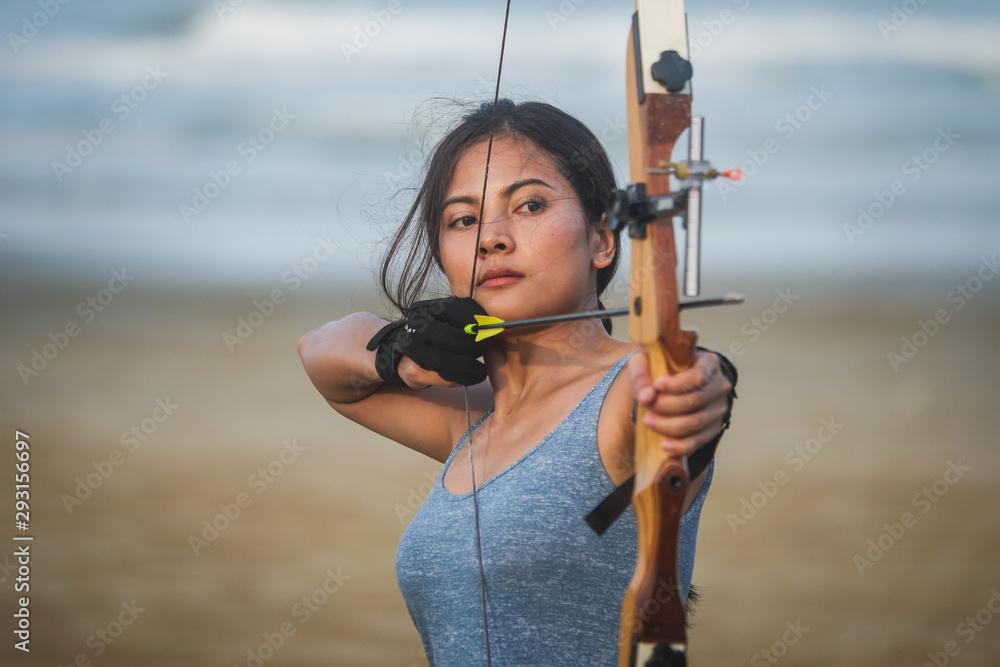 Fototapeta Asian Archery woman with bow shooting on the beach