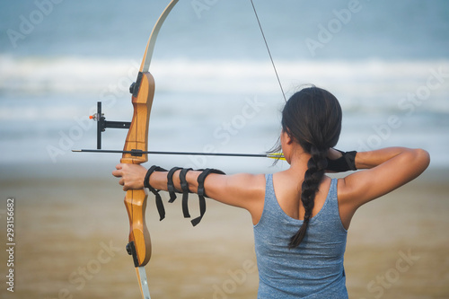 Asian Archery woman with bow shooting on the beach Canvas Print