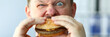 Funny bearded man with idiot facial expression eating big burger with enjoyment portrait