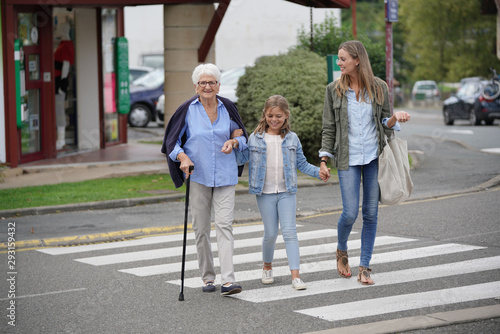Vászonkép Grandmother, mother and daughter crossing the street