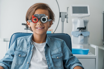 Portrait of smiling young boy undergoing eye test with spectacles in medical clinic