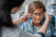 Female caucasian doctor putting glasses on little boy in clinic