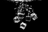 Ice cubes falling into the water. Ice cubes in water on a black background