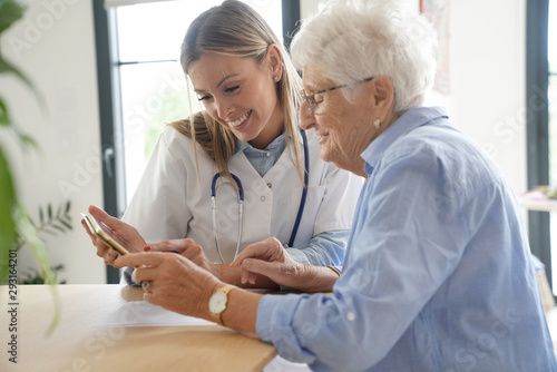 Elderly woman with nurse at home looking at tablet Wallpaper Mural