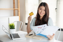 Happy Asian Young Woman Smiling Holding So Many Expenses Bills Such As Electricity Bill,.water Bill,internet Bill And Cell Phone Bill With Easy Life To Payment Credit Card On Her Hand
