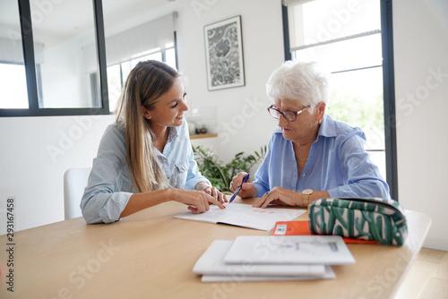 Obraz na plátně Homehelp assisting elderly woman with paperwork