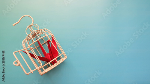 Fotografie, Obraz  Top view of a red origami crane inside a small metal bird cage, with the cage door opened