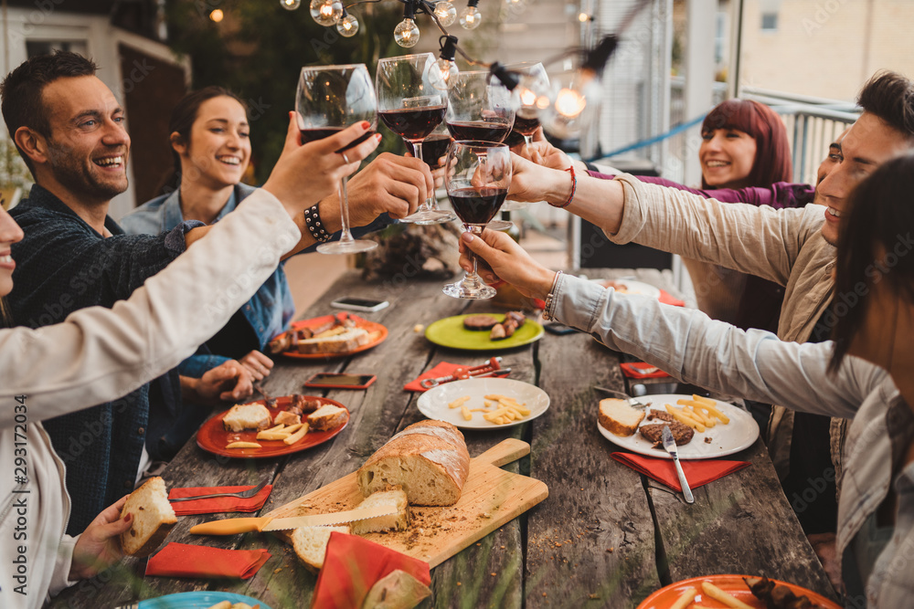 Fototapeta Group of young people having lunch on a terrace of an apartment at sunset - Millennials having fun together on a day of celebration - Toast with glasses of red wine
