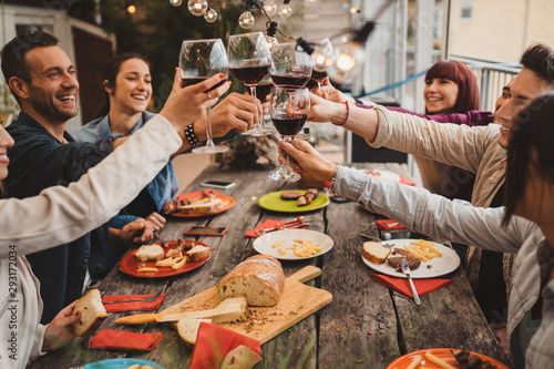 Group of young people having lunch on a terrace of an apartment at sunset - Millennials having fun together on a day of celebration - Toast with glasses of red wine - 293172034