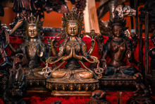 Buddhist Figurines And Masks Of Mythological Characters In Gold And Bronze On A Burgundy With A Red Background