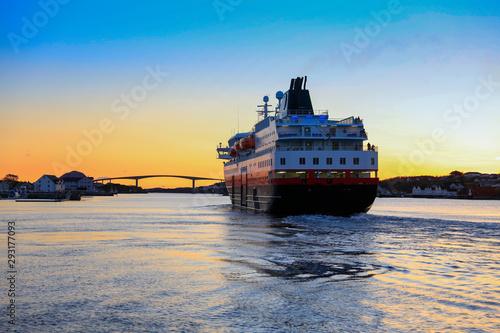 Coastal ships depart from Bronnoysund harbor in sunset, Northern Norway Fototapet