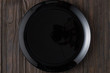 Empty luxury black plate on wooden background, view from above.
