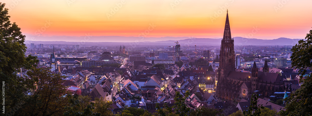 Fototapeta Germany, XXL panorama of skyline of freiburg im breisgau by night after sunset with red sky in magical twilight from above