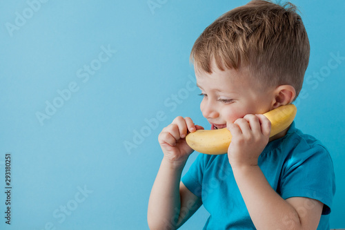 Tuinposter Aap Little Boy tries to speak by means of a banana instead of phone.