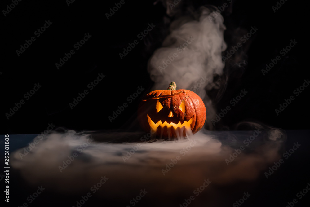 Fototapeta Halloween, orange pumpkin with a scary luminous face on a dark background. Thick gray smoke comes out and spreads across the black table. A close-up of a flashlight on the eve of all the saints