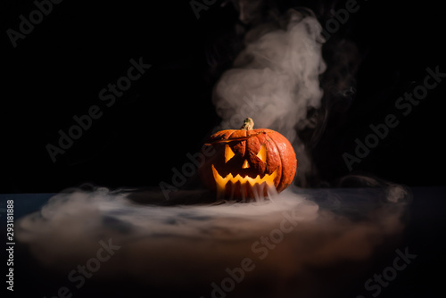Stampa su Tela  Halloween, orange pumpkin with a scary luminous face on a dark background