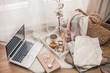 Toned photo. Autumn decor. A laptop, a mug of hot tea, a bun, candles. Cozy. Autumn.