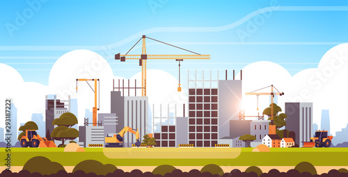 Obraz modern construction site with cranes tractor and bulldozer unfinished building exterior sunset background flat horizontal - fototapety do salonu