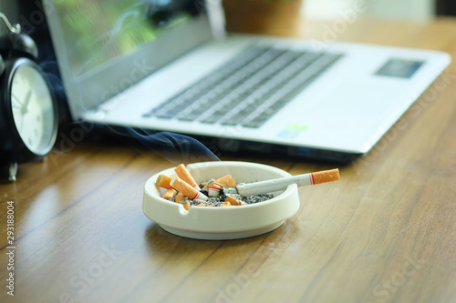 Many cigarette in white ashtray on the desk with laptop computer Wallpaper Mural