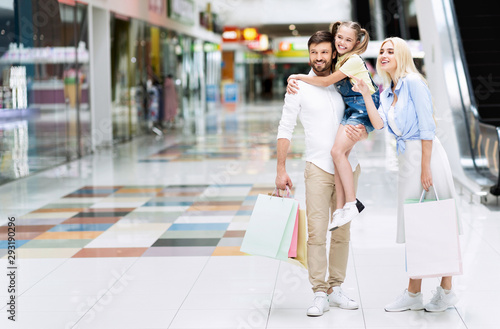 Valokuva  Wife Pointing Finger While Husband Carrying Daughter Shopping In Hypermarket