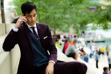 Young Businessman Sitting On Riverwalk Talking On Phone, Chicago, Illinois, United States