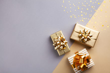Golden Gift Or Present Boxes With Golden Bows And Star Confetti Top View. Christmas Background. Flat Lay.