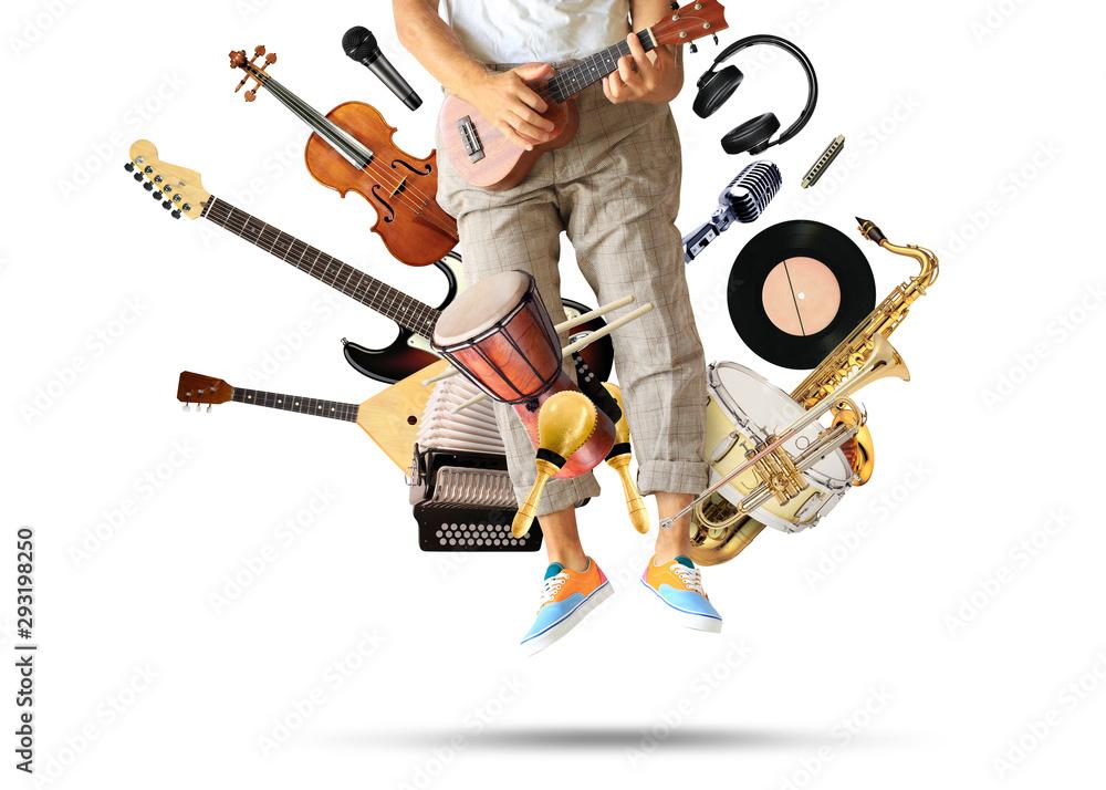 Fototapeta Young man plays guitar among musical instruments