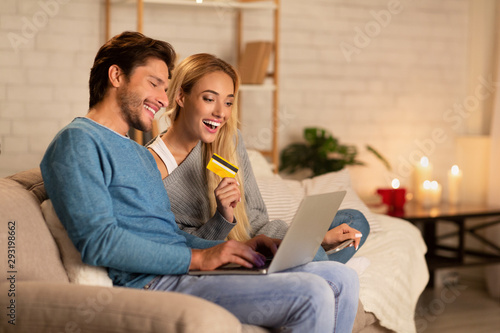 Happy Spouses Using Laptop And Online Shopping Card At Home - 293198662