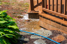 Puddle Of Brown Water With Soap Suds On A Brick Patio Near A Brown Wooden Deck. There Is Water Coming Off Of The Deck