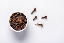 Dry Clove Spice In A White Bowl On A Grey Background, Close-up, Top View.