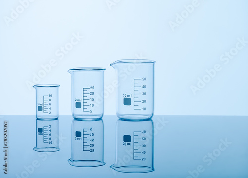 Photo Three empty measuring beakers sitting on a mirror blue surface