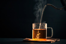 The Process Of Brewing Tea, Pouring Hot Water From The Kettle Into The Cup, Steam Coming Out Of The Mug, Water Droplets On The Glass, Black Background