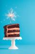 Leinwanddruck Bild - Chocolate cake slice with sparkler. Birthday cake on blue background