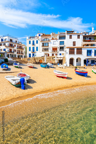 Photo Fishing boats on beach in Port Bo with colorful houses of old town of Calella de