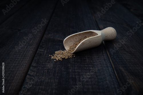 Wooden scoop with anise on a dark wooden table Canvas Print