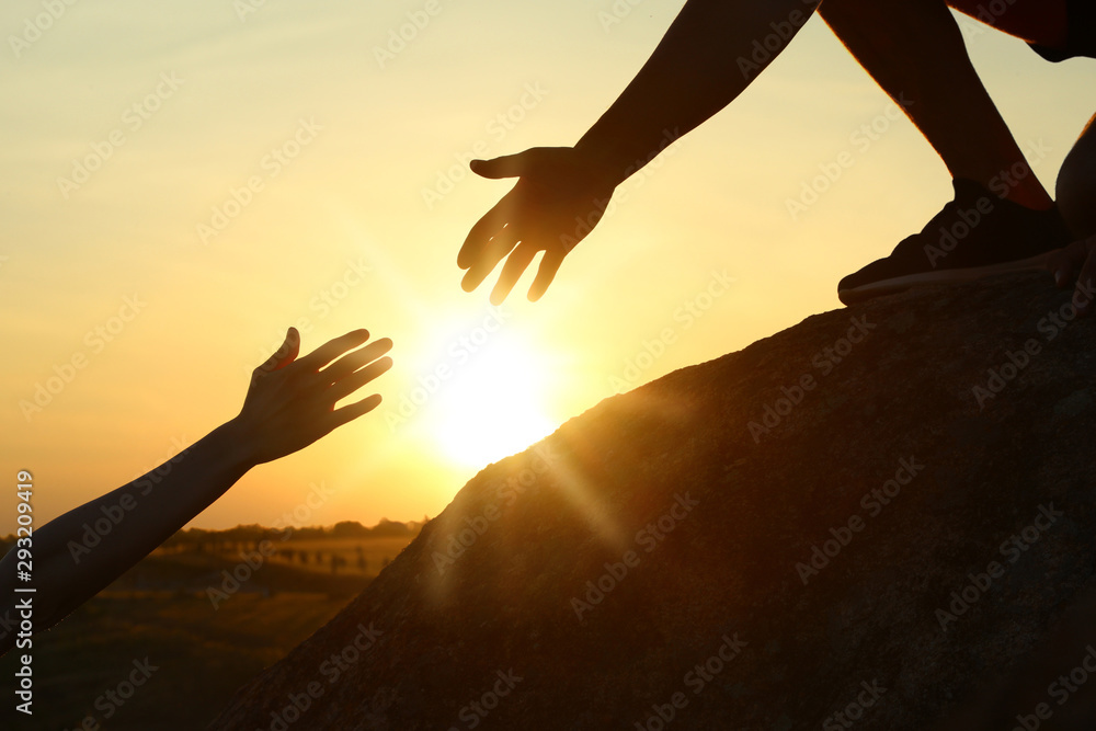Fototapeta Hiker helping friend outdoors at sunset. Help and support concept