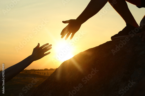 Obraz na plátně Hiker helping friend outdoors at sunset. Help and support concept
