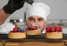 Male Pastry Chef Sprinkling Desserts With Sugar Powder In Kitchen