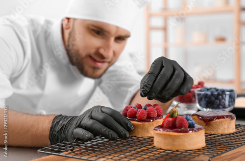 Fototapeta Male pastry chef preparing desserts at table in kitchen
