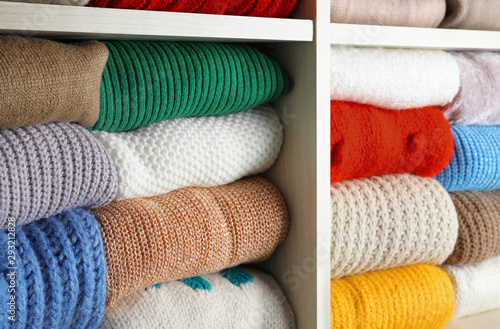 Canvastavla Folded colorful winter sweaters on shelves as background