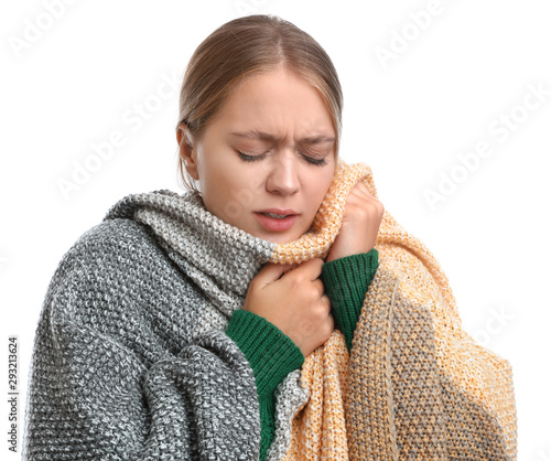 Photo Young woman wrapped in warm blanket suffering from cold on white background