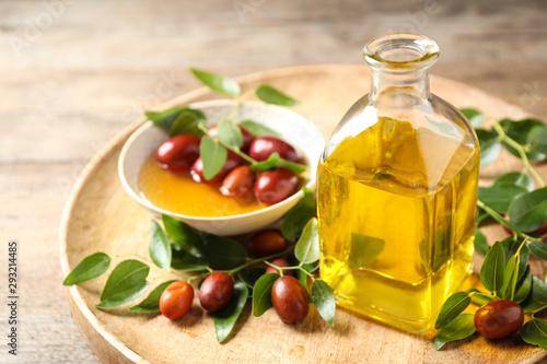 Fotografie, Obraz Glass bottle with jojoba oil and seeds on wooden table
