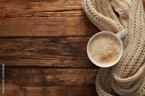 Photo Top view of coffee and knitted scarf on wooden table, space for text