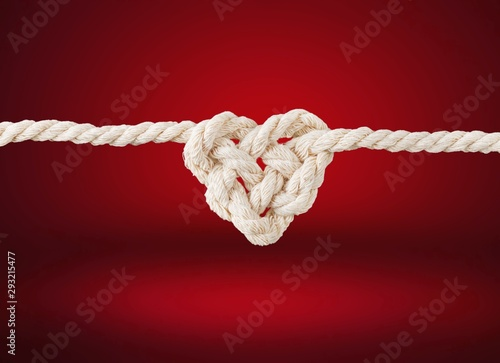 Cuadros en Lienzo  White rope in heart shape knot on background. Love concept.
